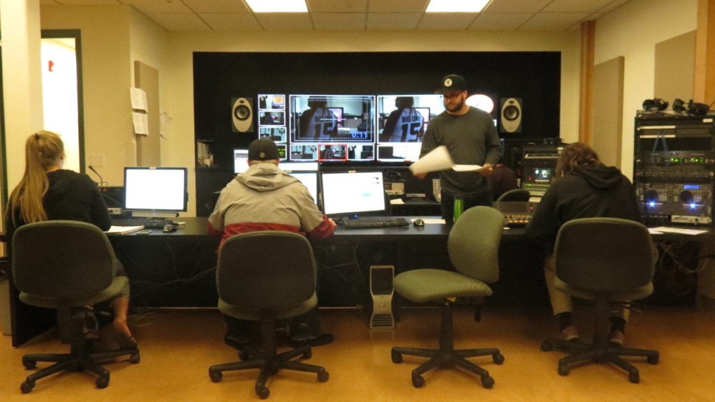 photo of j-school broadcast students working on video production on their screens.