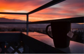 Photo shows a darkly shadowed mug of tea sitting on a railing with a bright orange sunset in the distance