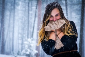 A self portrait of Felstet clutching a scarf to her face while standing in the snow