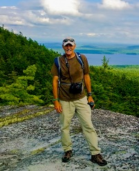 photo of Ken Wells standing on a mountain edge after a hike.