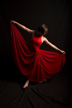 Photo of woman in dark room in a vibrant red dress