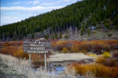 """Landscape photo with a sign in the foreground that reads """"Welcome to Blackfeet Indian Country."""""""