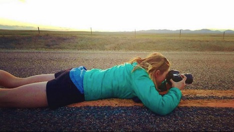 Native News photographer Sophie Tsairis lays in the middle of a deserted highway to snap a photo of the landscape.