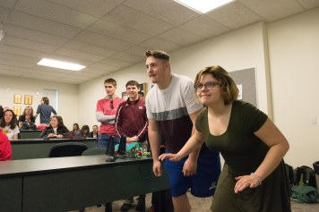 "Students rush for the buzzers during Dennis Swibold's ""Fake News Game Show."" Photo by Jamie Drysdale."